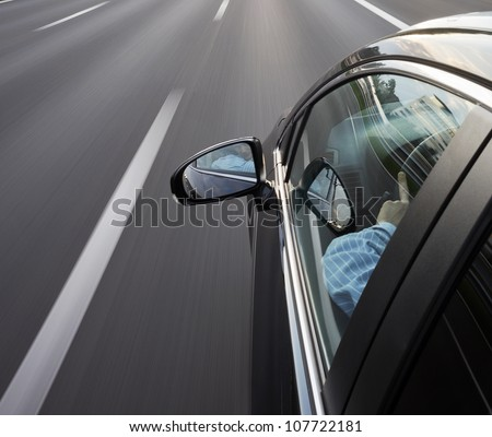 Car speeding along the motorway, with the driver looking in his mirror