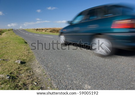 Car speeding on empty road. Dartmoor, UK.