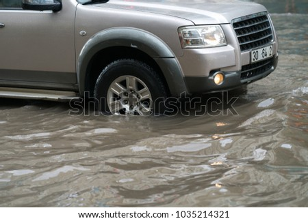 Car splashes through a large puddle on a flooded street #1035214321
