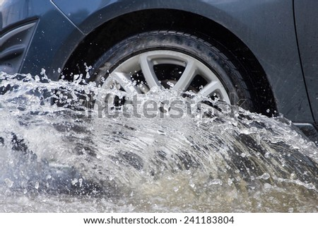 Car splashes through a large puddle on a flooded street  #241183804