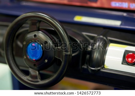 car steering of console of racer game machine in game arcade #1426572773