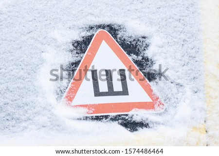 Car sticker studded tires on the snow-covered rear glass of the car in the winter. Russian warning sign #1574486464