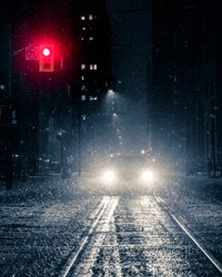 Car stopped at red light in downtown urban city during large snow storm. Winter scene with heavy snowfall. Toronto, Ontario, Canada