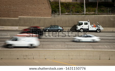 Car stranded on shoulder of freeway with tow truck stopped behind it and traffic blurred as cars speed by the scene