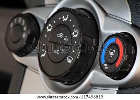 Car temperature conditioner with panel and blue red knob . Focus on first regulation wheel