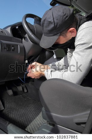 Car thief hot wiring the electrical circuits on the ignition of a car as he prepares to steal it - stock photo