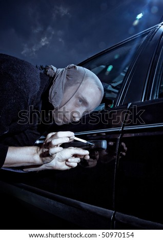 Car thief picking a lock - stock photo