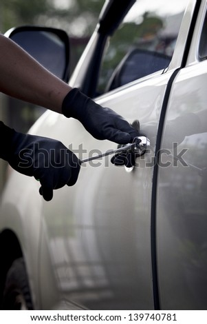 Car thief ,Shot of a male using a tool to break into a car.