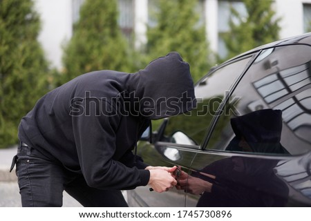 Photo of  Car thief steal car breaking door criminal job burglar Hijacks  Auto thief black balaclava hoodie trying  break into vehicle screwdriver  Street crime violence gangster robber automobile parking