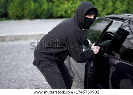 Car thief steal car breaking door criminal job burglar Hijacks  Auto thief black balaclava hoodie trying  break into vehicle screwdriver  Street crime violence gangster robber automobile parking Сток-фото ©
