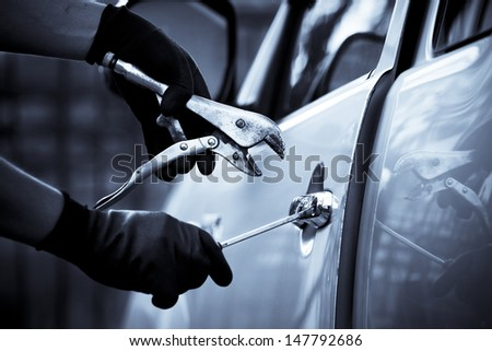 Car thief using a tool to break into a car.