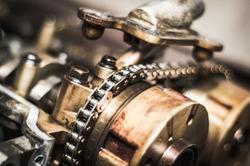 Car timing chain in cutaway engine. shiny metal
