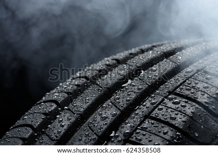 Car tire covered with water drops in the fog