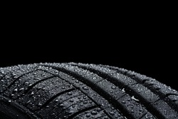 Car tire covered with water drops on black background