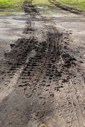 Car tire imprints in black earth and grass in wet mud with puddles and sand. Sunny spring.