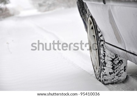 car tire in snow on the road does trace