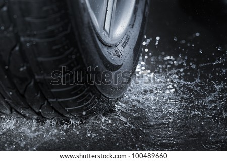 Car tire splashing in water. #100489660