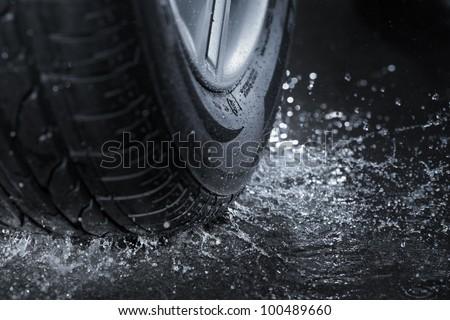 Car tire splashing in water.