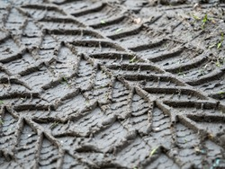 Car tire tracks on wet muddy  road.