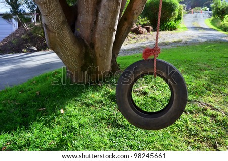 Car tire used as a swing on a tree in the garden. Concept photo of childhood, nostalgia, memory , past, life.Concept photo of childhood, nostalgia, memory , past, life, retro, vintage, home sweet home