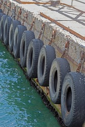 car tire with a metal chain on a old concrete sea pier