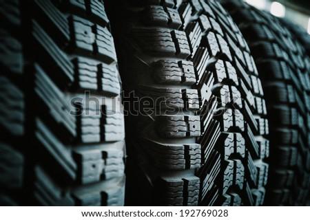 Car tires in a row on a shelf tire