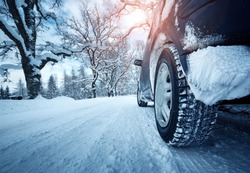 Car tires on winter road covered with snow
