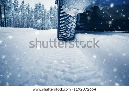 Car tires on winter road covered with snow. Vehicle on snowy way in the morning at snowfall #1192072654