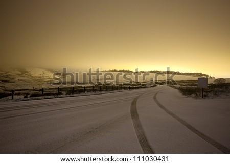 car tracks in snow at night