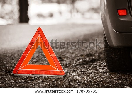 Car transportation. Breakdown of car transporation. Closeup of red warning triangle sign symbol on the forest road. #198905735