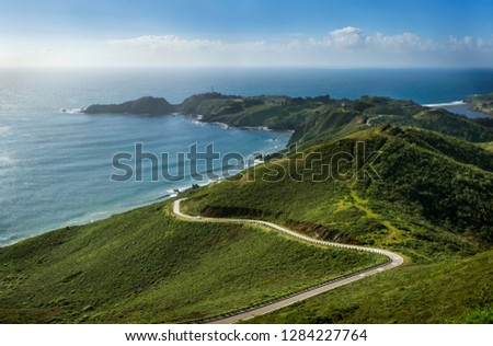 Car traveling along a winding road towards the tip of a peninsula in the countryside.