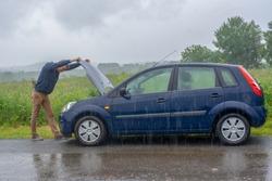 Car trouble in the rain. Broken car.