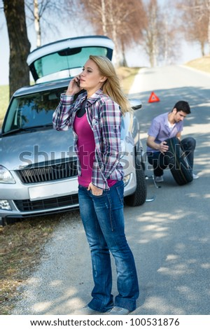 Car trouble woman calling road assistance man change broken wheel