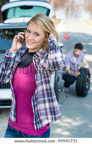 Car trouble woman calling road assistance man change broken wheel - stock photo