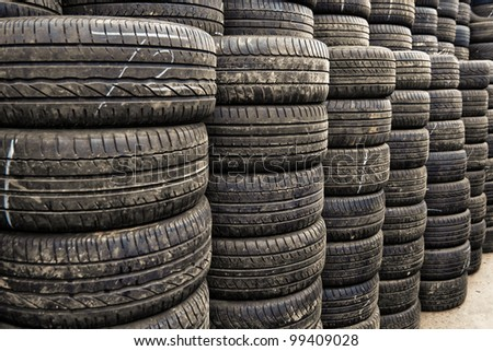 Car tyres stacked in a tyre distribution centre. Selective focus.