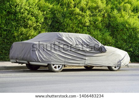 Car under a protective cover parked in the courtyard in sun weather, summer. The car on the side of the road under a protective cover on a green background of foliage bush #1406483234