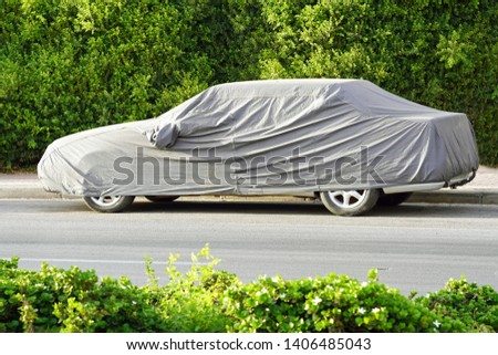 Car under a protective cover parked in the courtyard in sun weather, summer. The car on the side of the road under a protective cover on a green background of foliage bush #1406485043