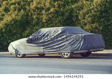 Car under a protective cover parked in the courtyard in sun weather. The car on the side of the road under a protective cover on a green background of foliage bush                          #1496144291