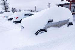Car under snow blocked in parking snowstorm winter frost.