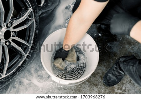 Car wash and detailing concept. Top view of washing tools in car wash service, white bucket with soap cleaning solution, special grille. Hand of male worker holding sponge for cleaning car rims Stock fotó ©