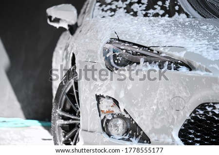Car wash concept. Front view of white sports car covered with water, washing foam, and soap on hood & bumper. Professional car detailing & commercial cleaning service concept. Wet car background.