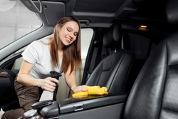 Car wash service, girl worker cleaning spray eco interior modern microfiber and console auto.