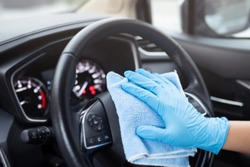 car wash,  worker hand wear glove cleaning console steering wheel with microfiber cloth blue. hygiene prevention  antibacterial of corona virus outbreak.
