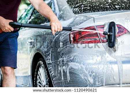 Car washing with brush and foam rear light on luxury automobile vehicle. #1120490621