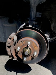 Car wheel hub and disc brake in rusted condition at tyre service workshop