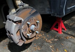 Car wheel hub and disc brake in rusted condition, with red jack stand on the foreground