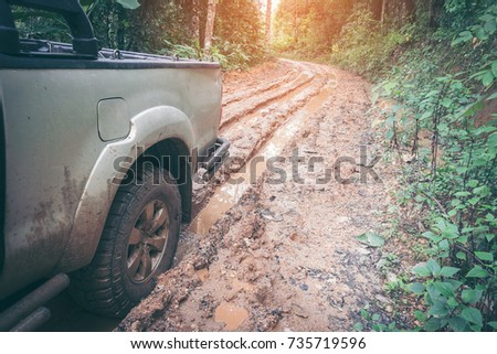 Car wheel on a dirt road. Off-road tire covered with mud, dirt terrain. Outdoor, adventures and travel suv. Car tire close-up in a countryside landscape with a muddy road. Four wheel truck in mud. Stock photo ©