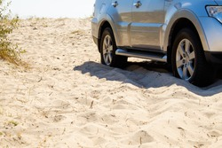 Car wheels on a sea beach sand. Off-road tire on summer seashore. Outdoor, adventures and travel suv. Close-up of car wheel on sandy dunes in countryside with ocean in background.