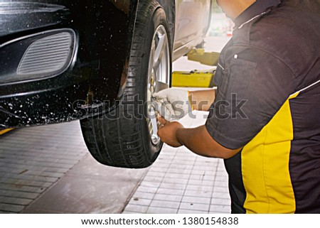 car wheels repair, selective focus on mechanic changing wheeled vehicles in garage or auto repair shop #1380154838