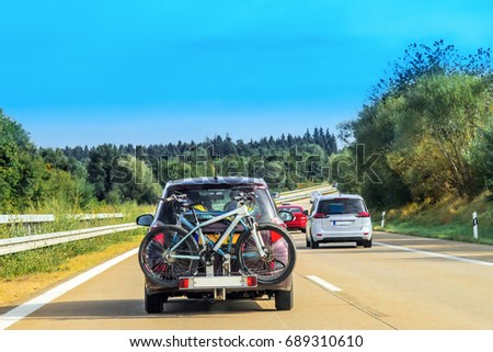 Car with bicycles in the highway in Switzerland.